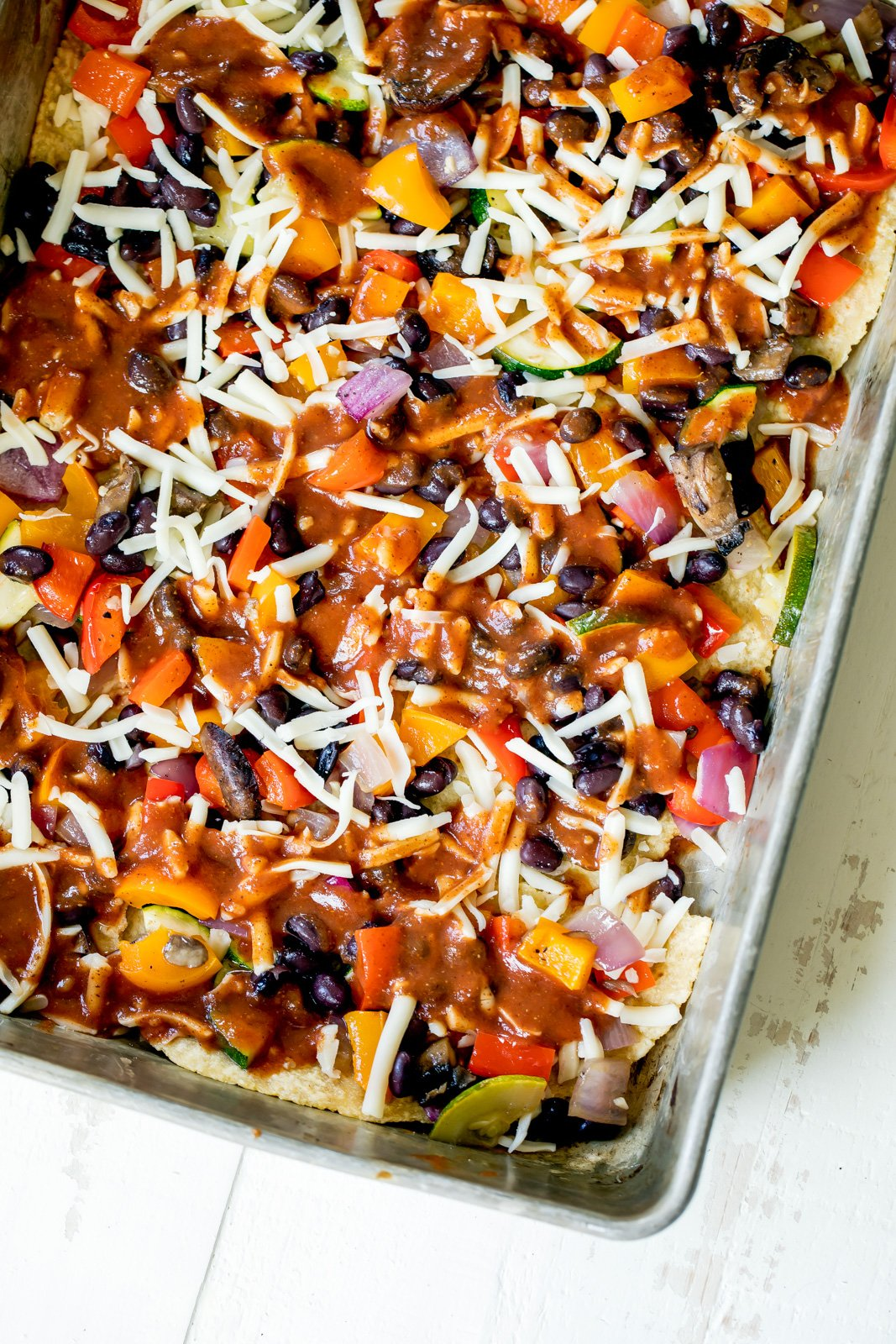 vegetarian enchilada casserole ready to bake in a dish
