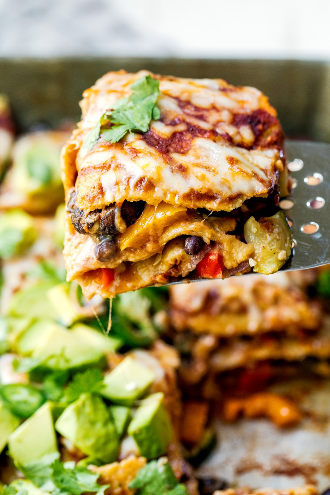 slice of veggie enchilada casserole being lifted by a spatula