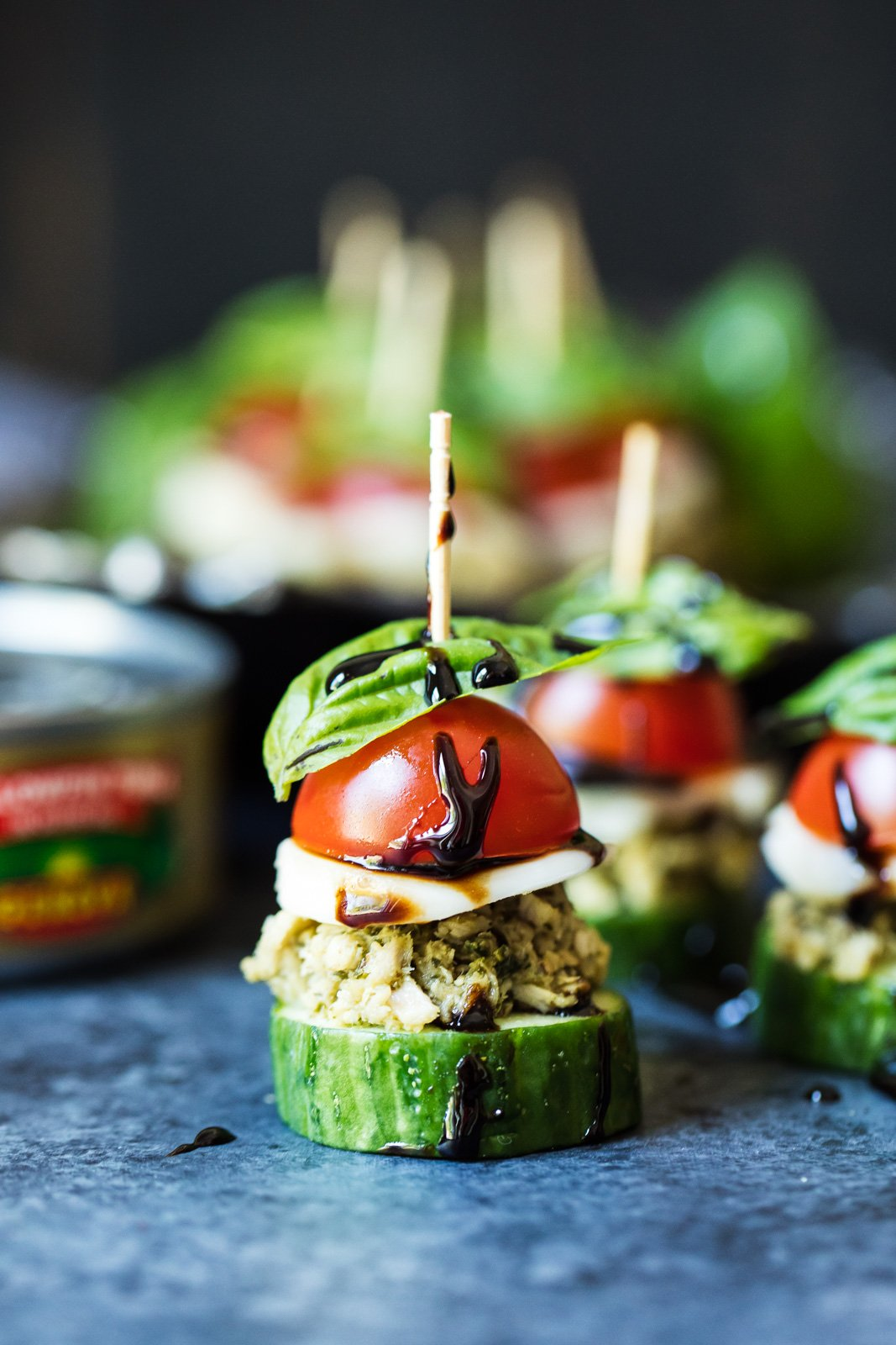 Quick and flavorful cucumber bites topped with delicious pesto flavored Genova tuna, fresh tomato and basil, creamy mozzarella, and a drizzle of homemade balsamic reduction.
