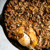 gluten free peach crisp in a skillet with a spoon
