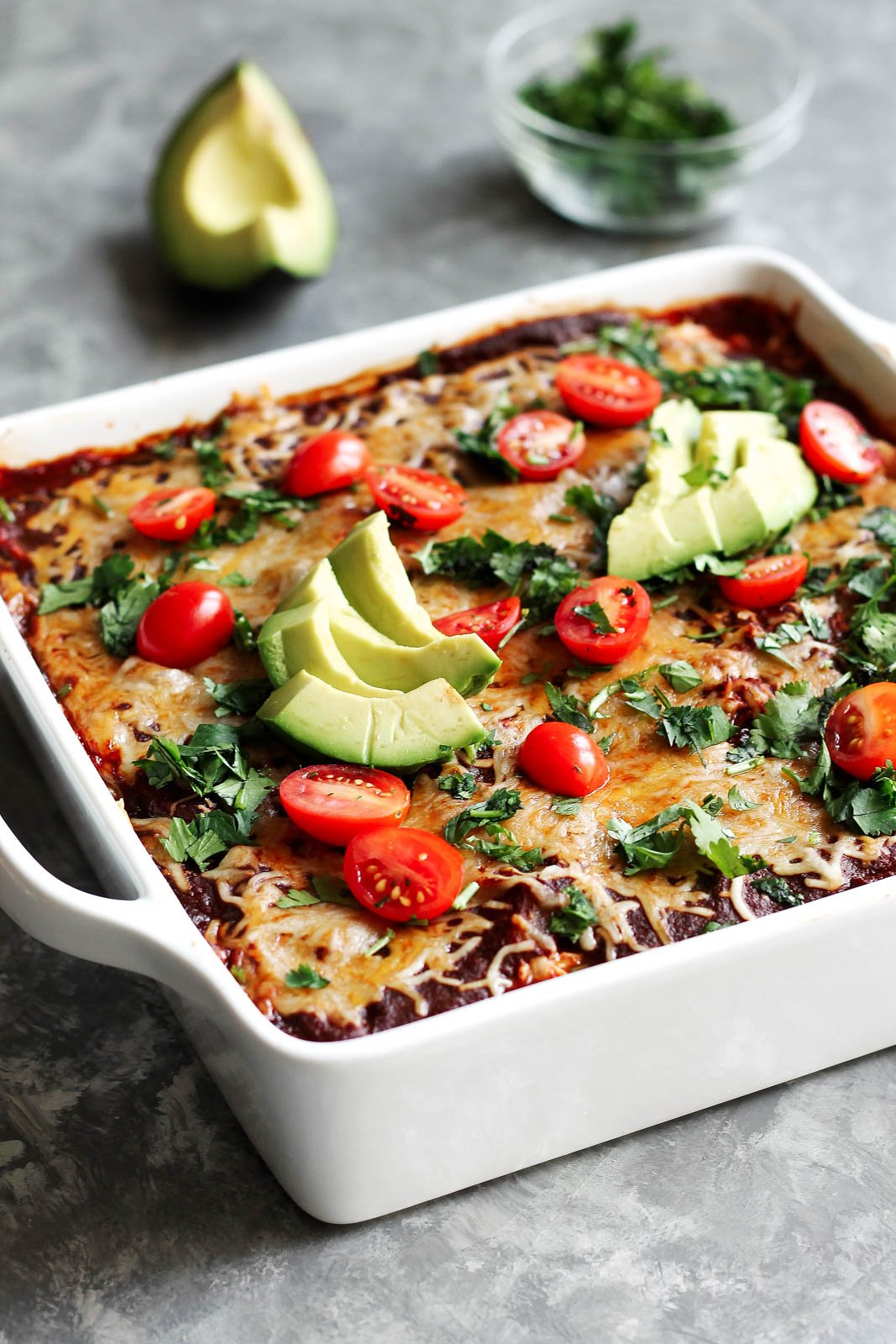 Enchilada casserole in a white baking dish with avocado and tomatoes