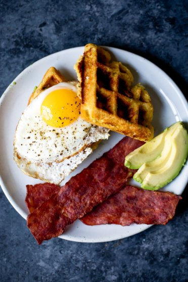 zucchini cornbread waffles on a plate with egg, avocado, and turkey bacon