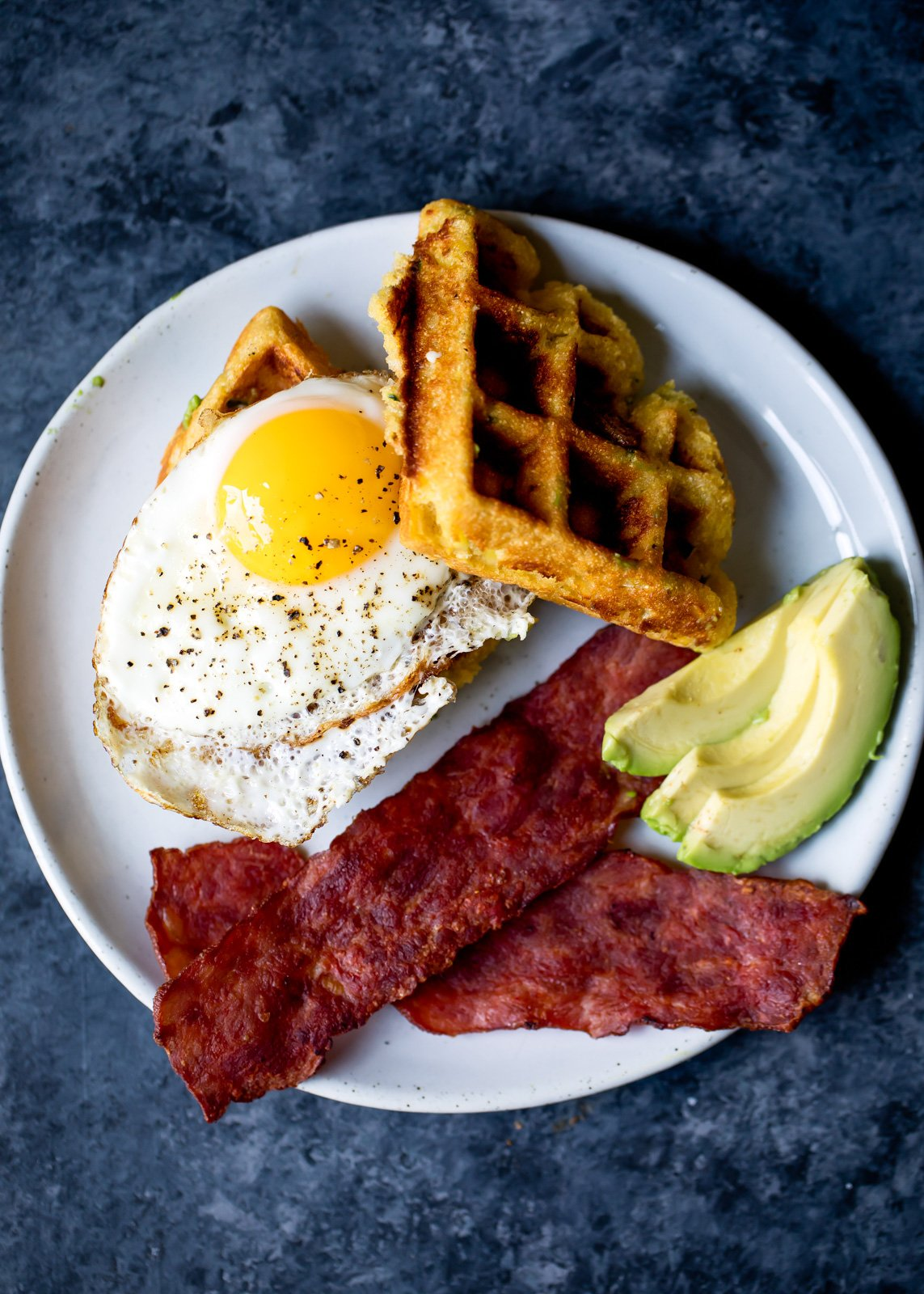 A savory breakfast featuring whole grain honey jalapeno zucchini cornbread waffles. Delicious, filling and perfect when topped with a fried egg and a side of turkey bacon!