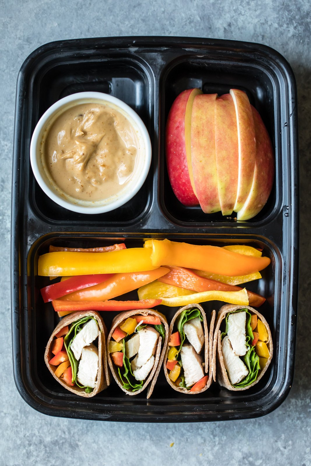 chicken wrap, peppers, apple slices, and peanut butter in a bento box