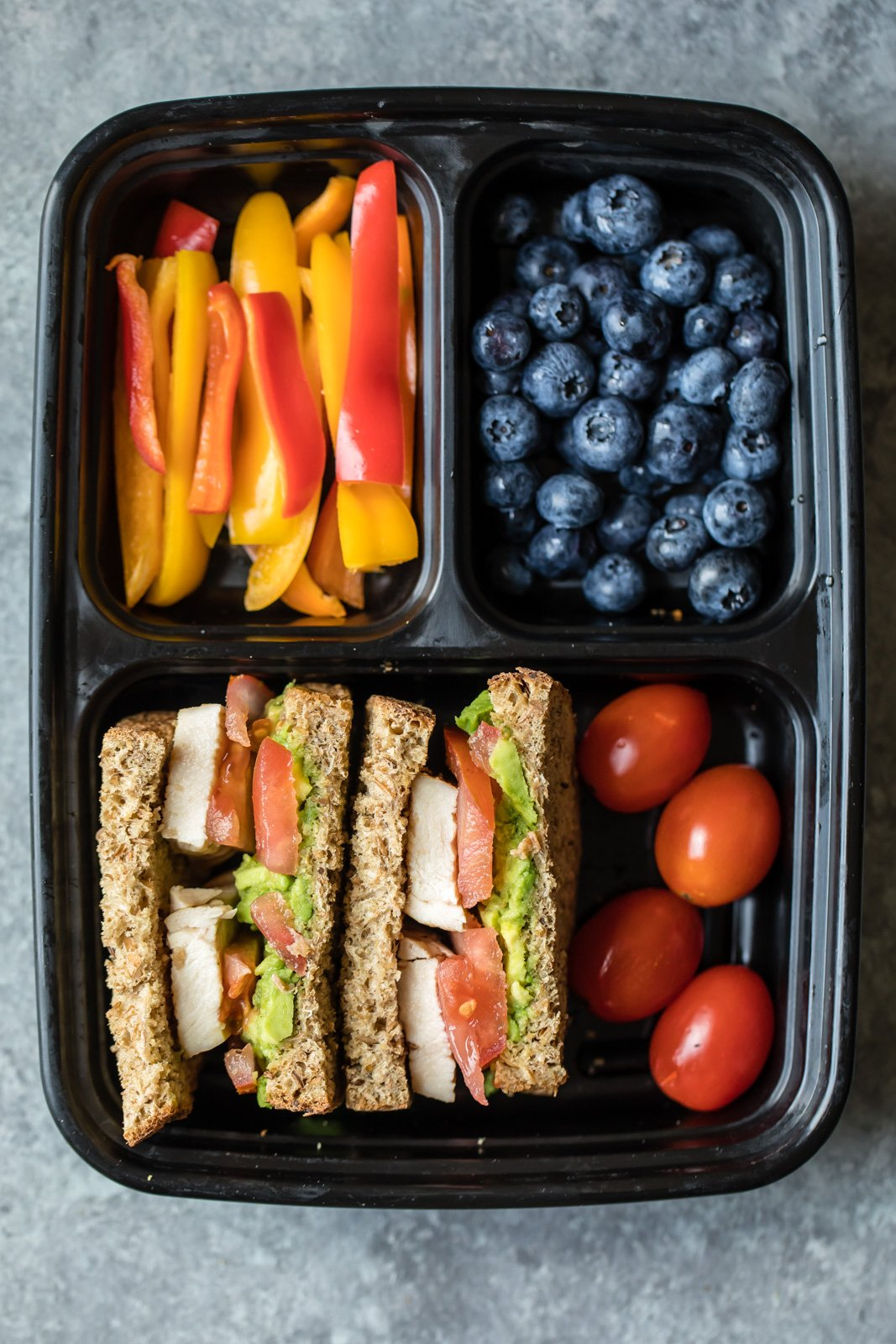 chicken sandwich, pepper slices, grape tomatoes, and blueberries in a bento box