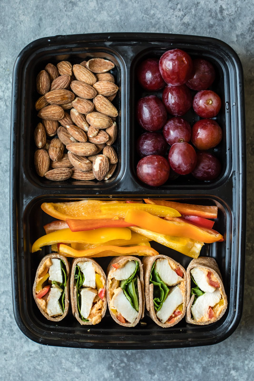 chicken wrap, pepper slices, grapes, and almonds in a bento box