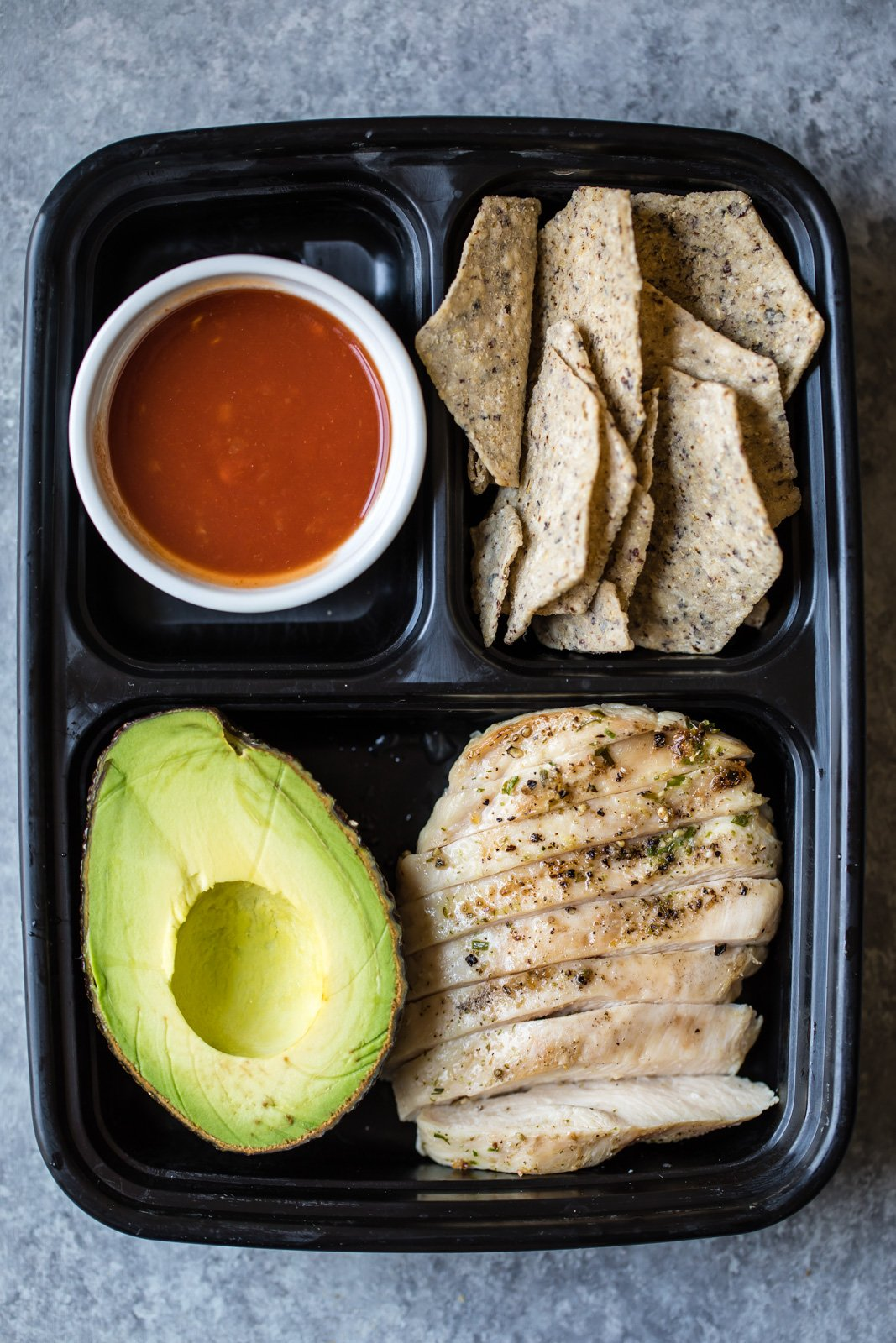tortilla chips, avocado, chicken, and salsa in a bento box