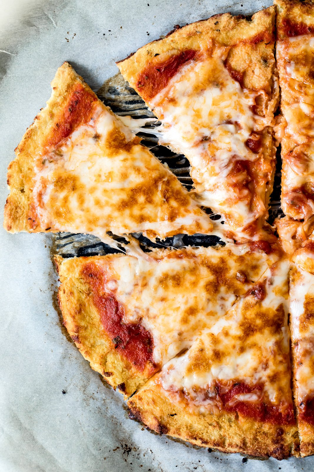 The BEST cauliflower pizza crust — so flavorful and surprisingly easy to make. Low carb, nutritious, fiber & protein packed. Topped the crust with whatever your heart desires. You're going to be making this again and again!