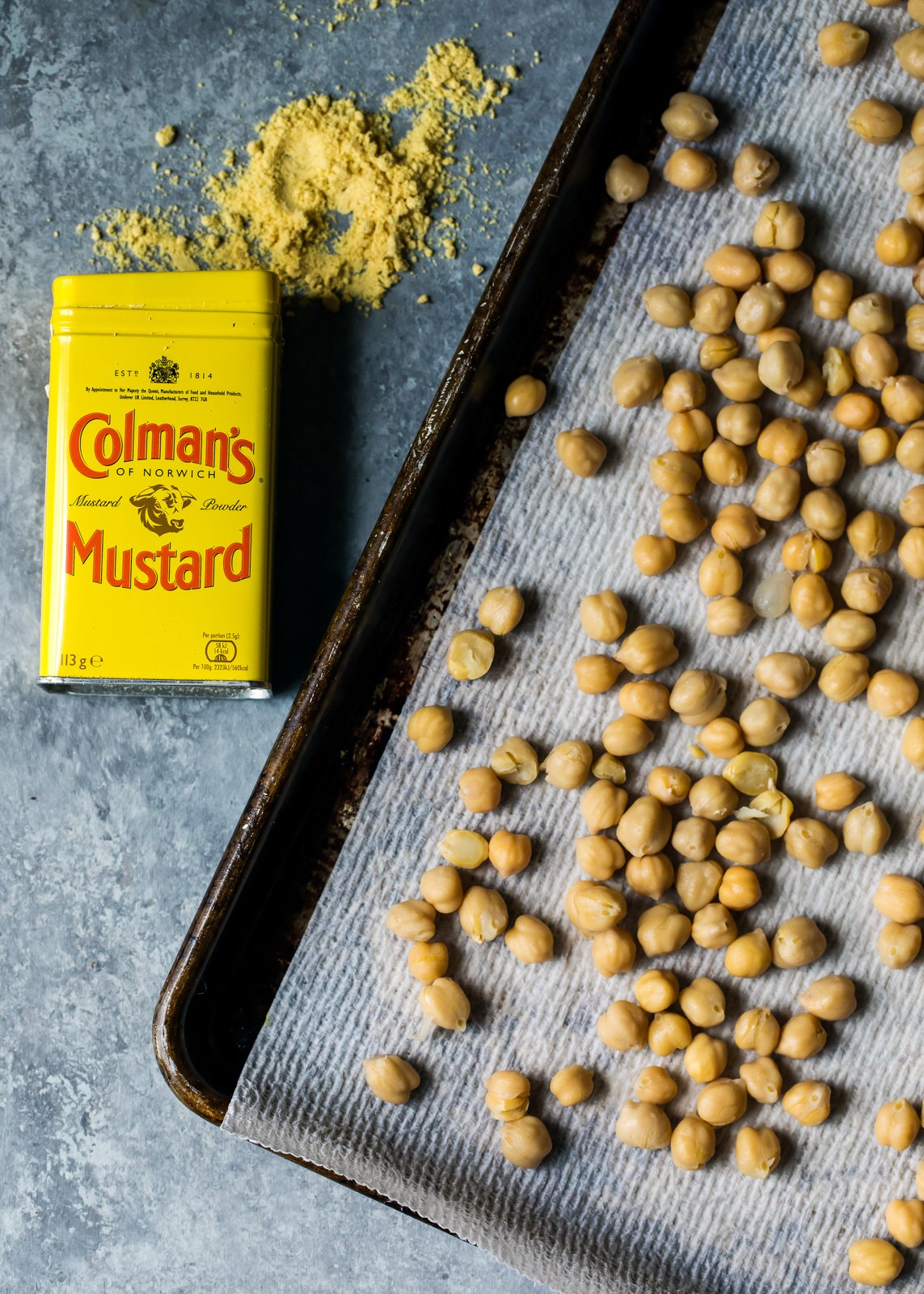 Spicy Roasted Chickpeas on a baking sheet next to Colman's Mustard