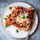 The BEST turkey lasagna EVER. Made with a homemade tomato basil sauce packed with fresh herbs & italian spices, layered with lean ground turkey, mozzarella, creamy ricotta and a touch of parmesan. Perfect for serving crowds, family style dinners, or freezing for later!