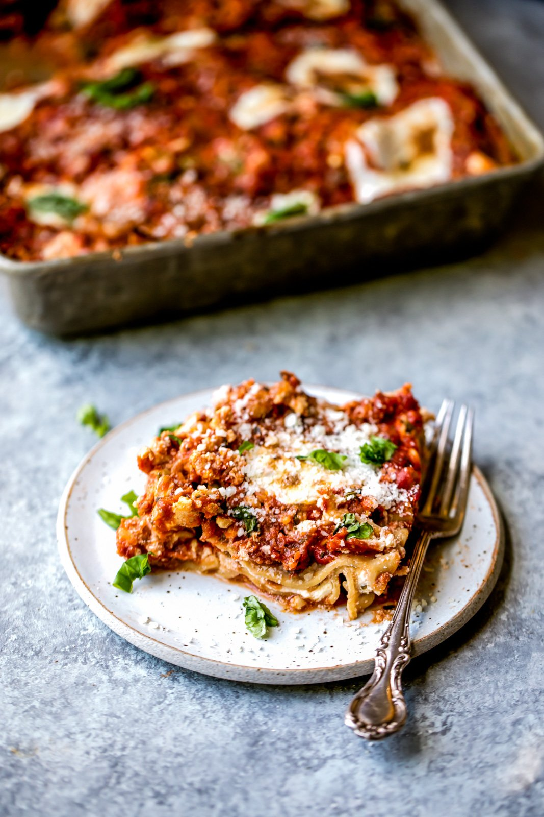 turkey lasagna on a plate with a fork and a pan of lasagna in the background