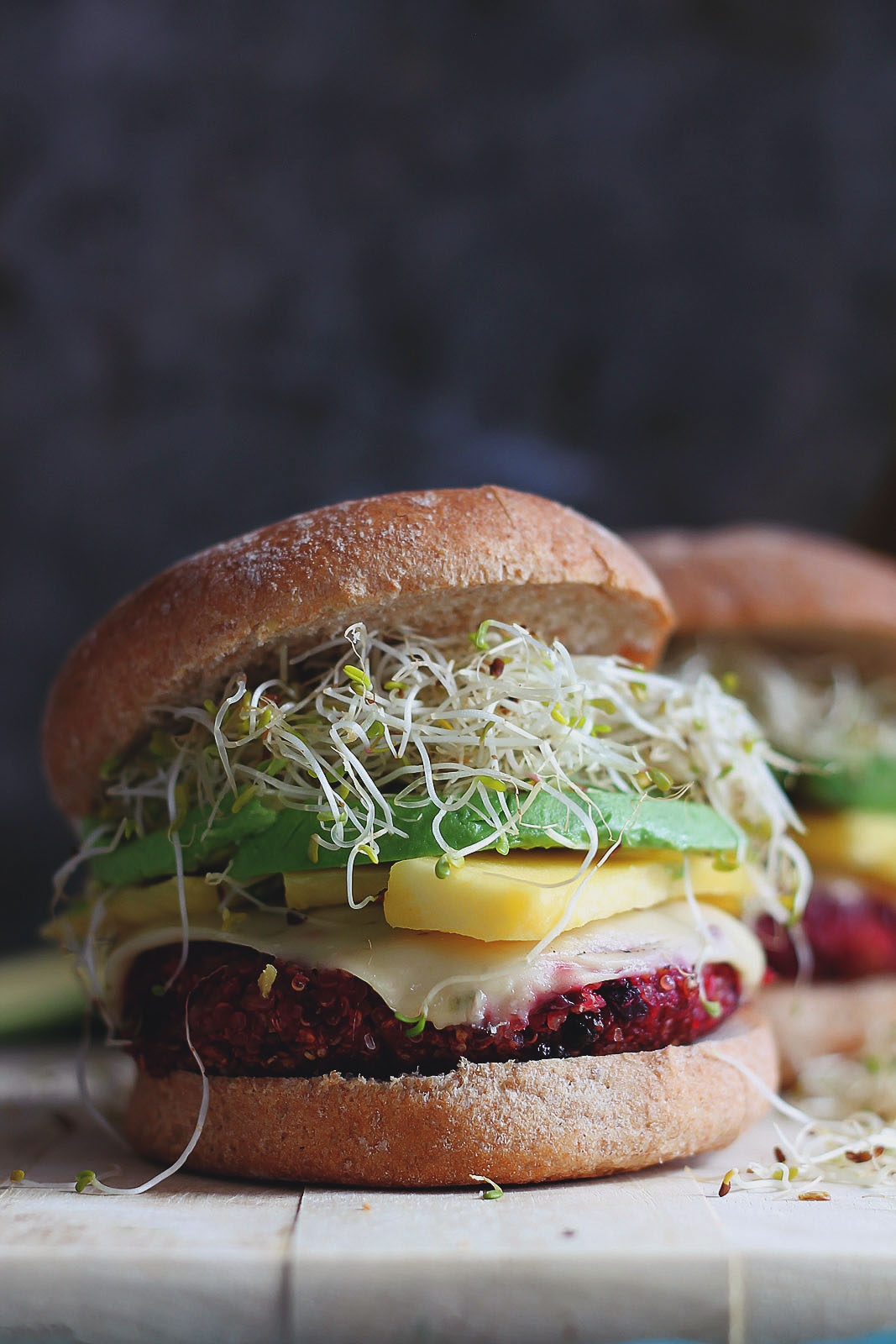 Beet burger topped with sprouts, avocado, mango and cheese