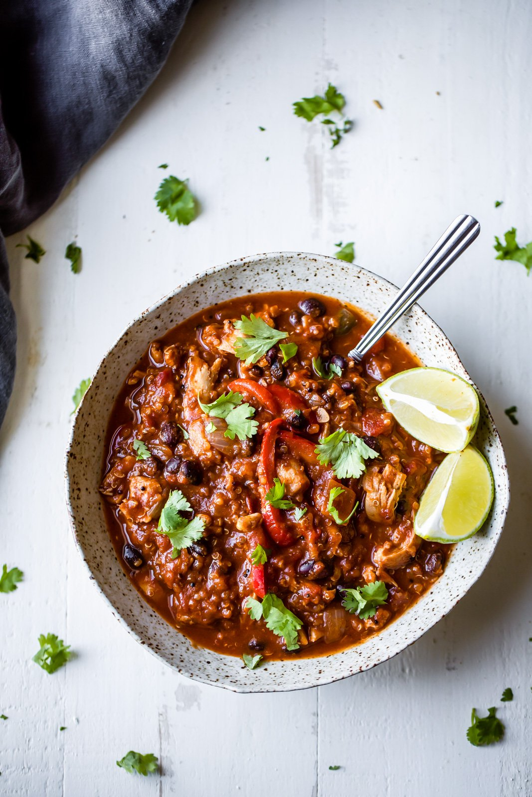 Chili in a bowl with lime wedges
