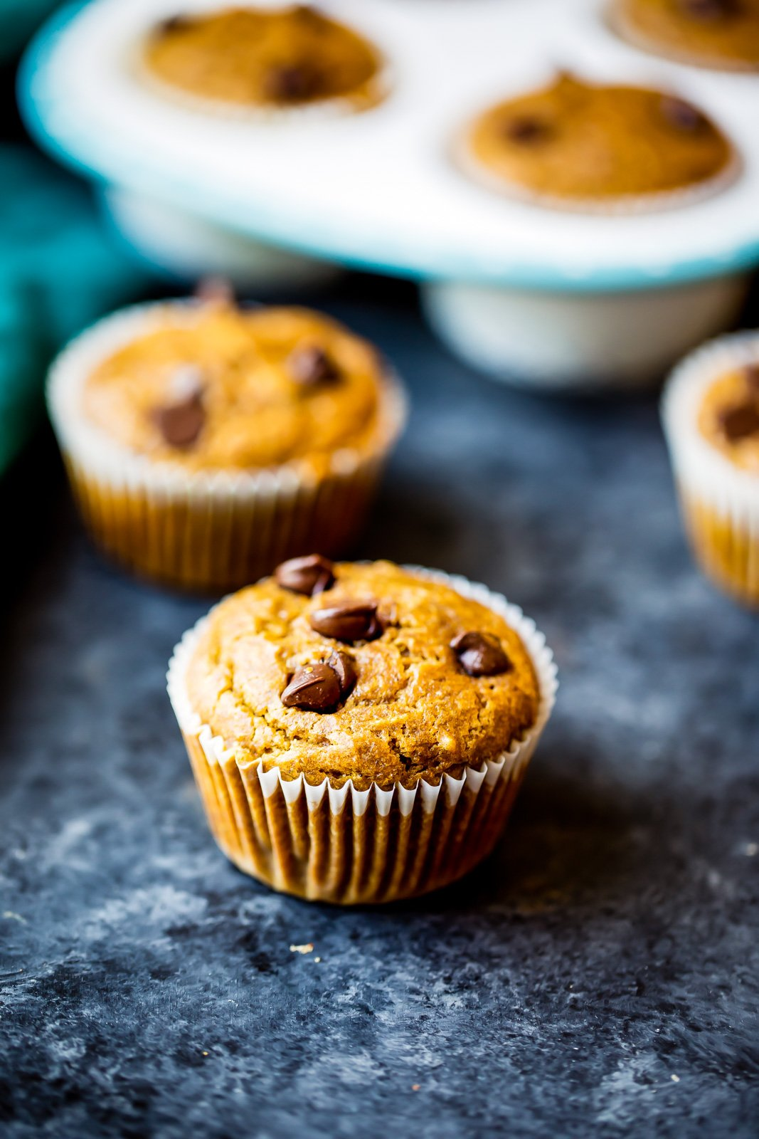 Pumpkin chocolate chip muffins in a muffin tin and on a board
