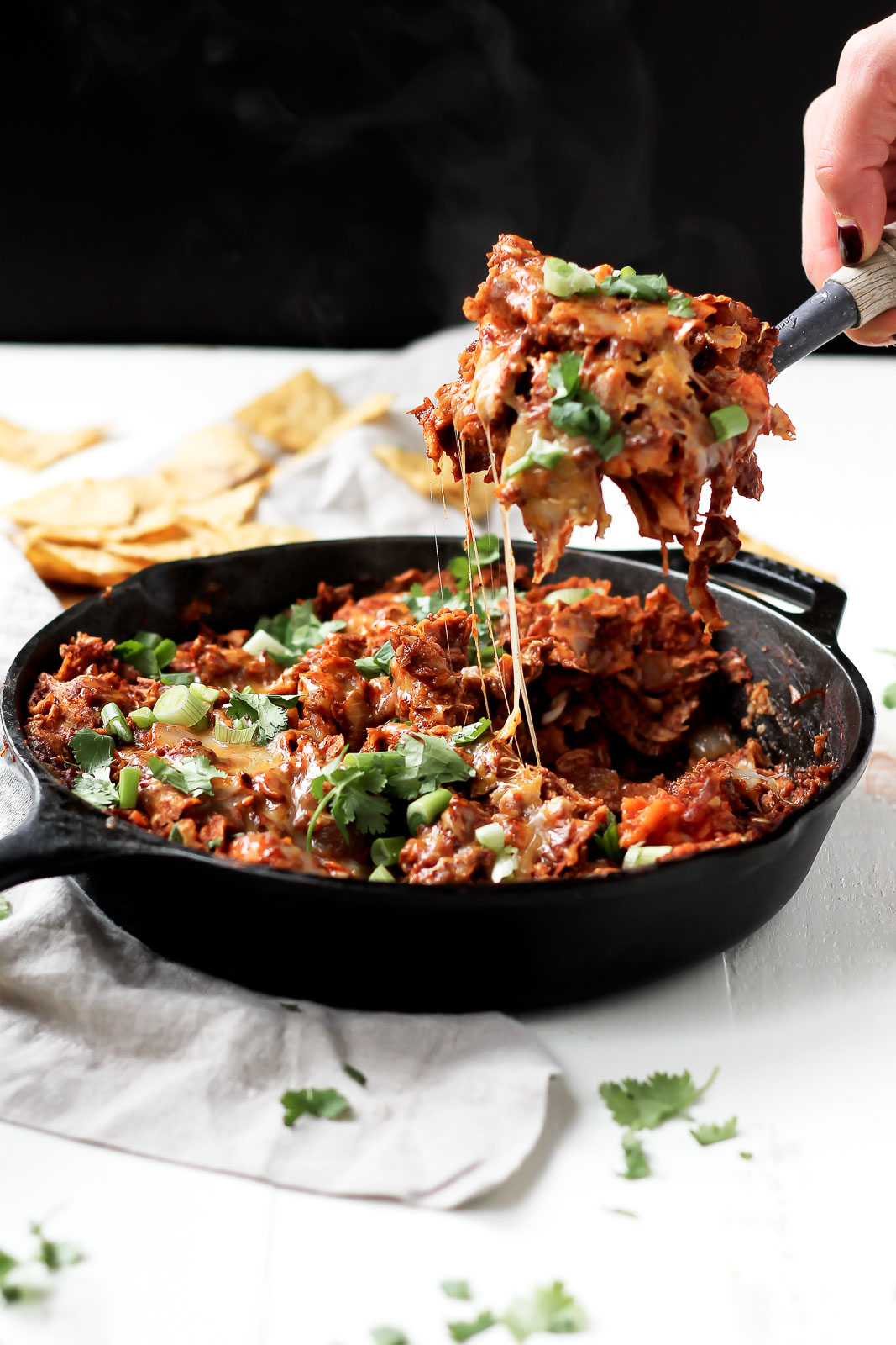scooping sweet potato turkey enchilada casserole out of a skillet