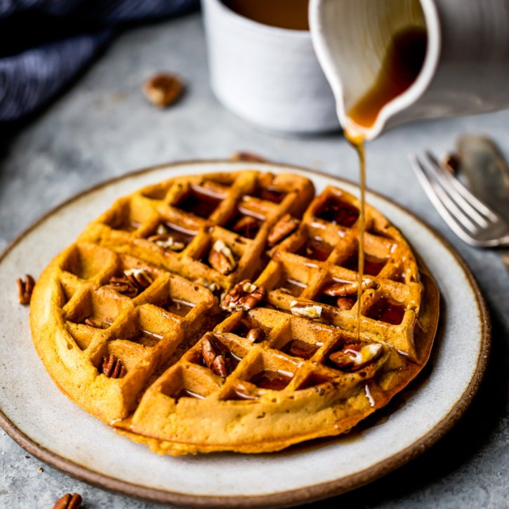 Freezer friendly healthy pumpkin waffles with cozy spices + a touch of maple syrup. These fluffy waffles will be your go-to fall breakfast.