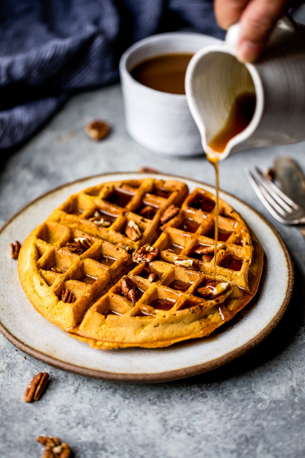 drizzling syrup on healthy pumpkin waffles
