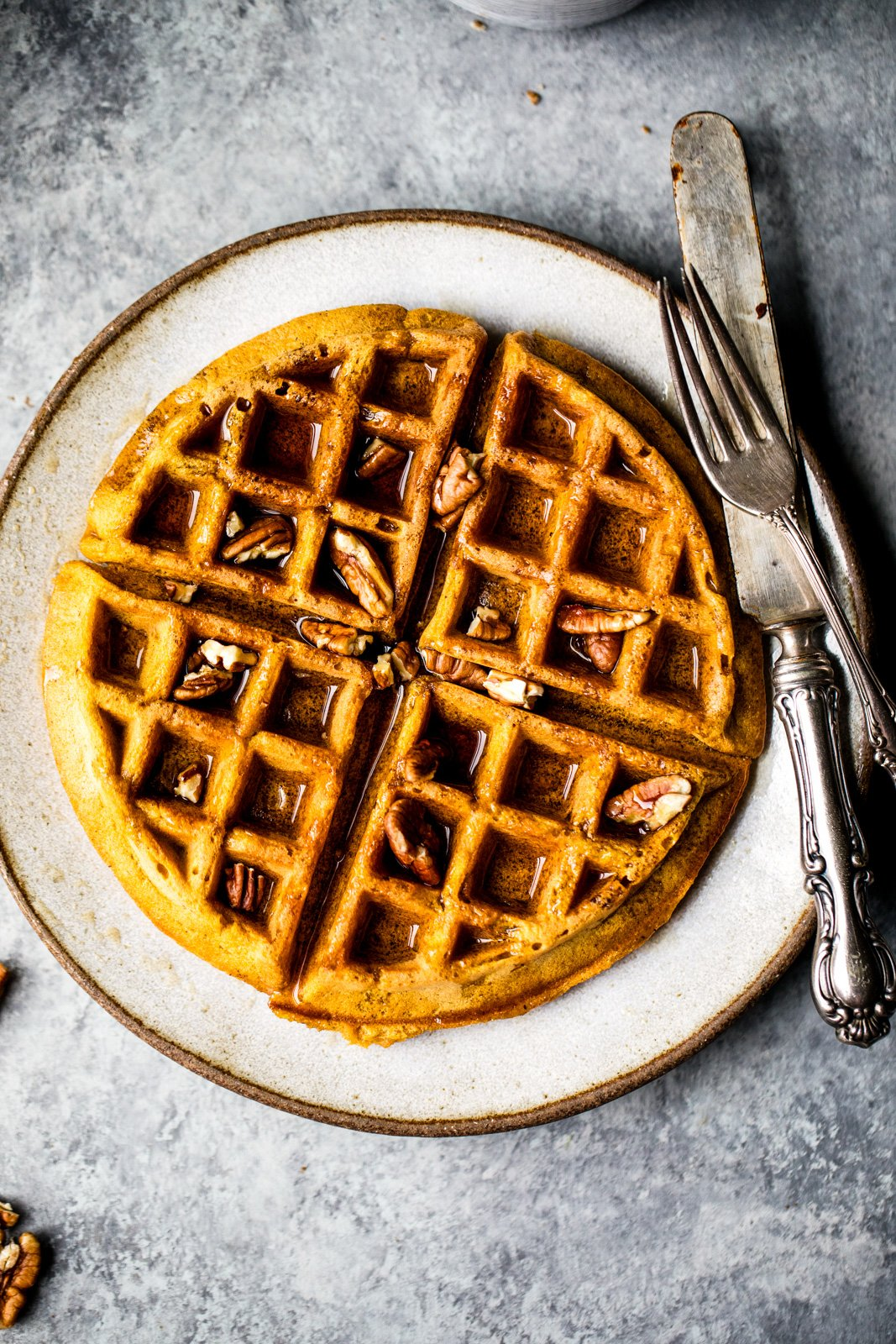 healthy pumpkin waffles on a plate topped with pecans