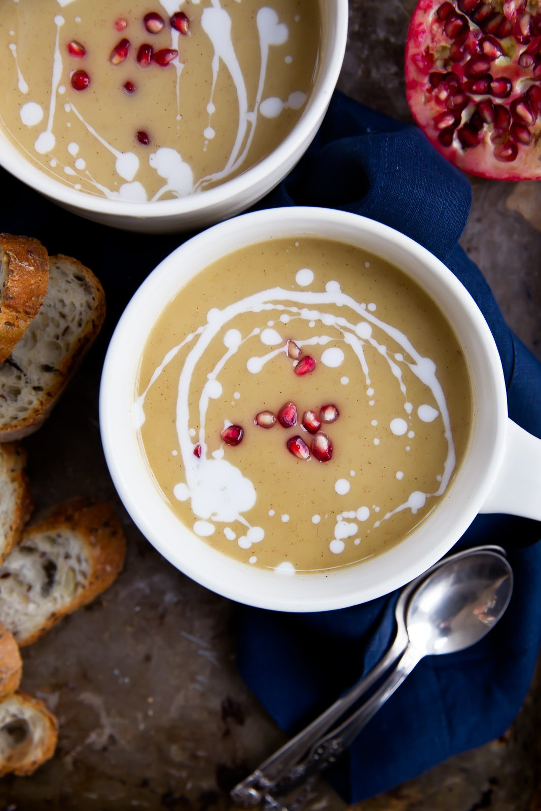 white bean soup with pomegranate seeds on top in a white mug