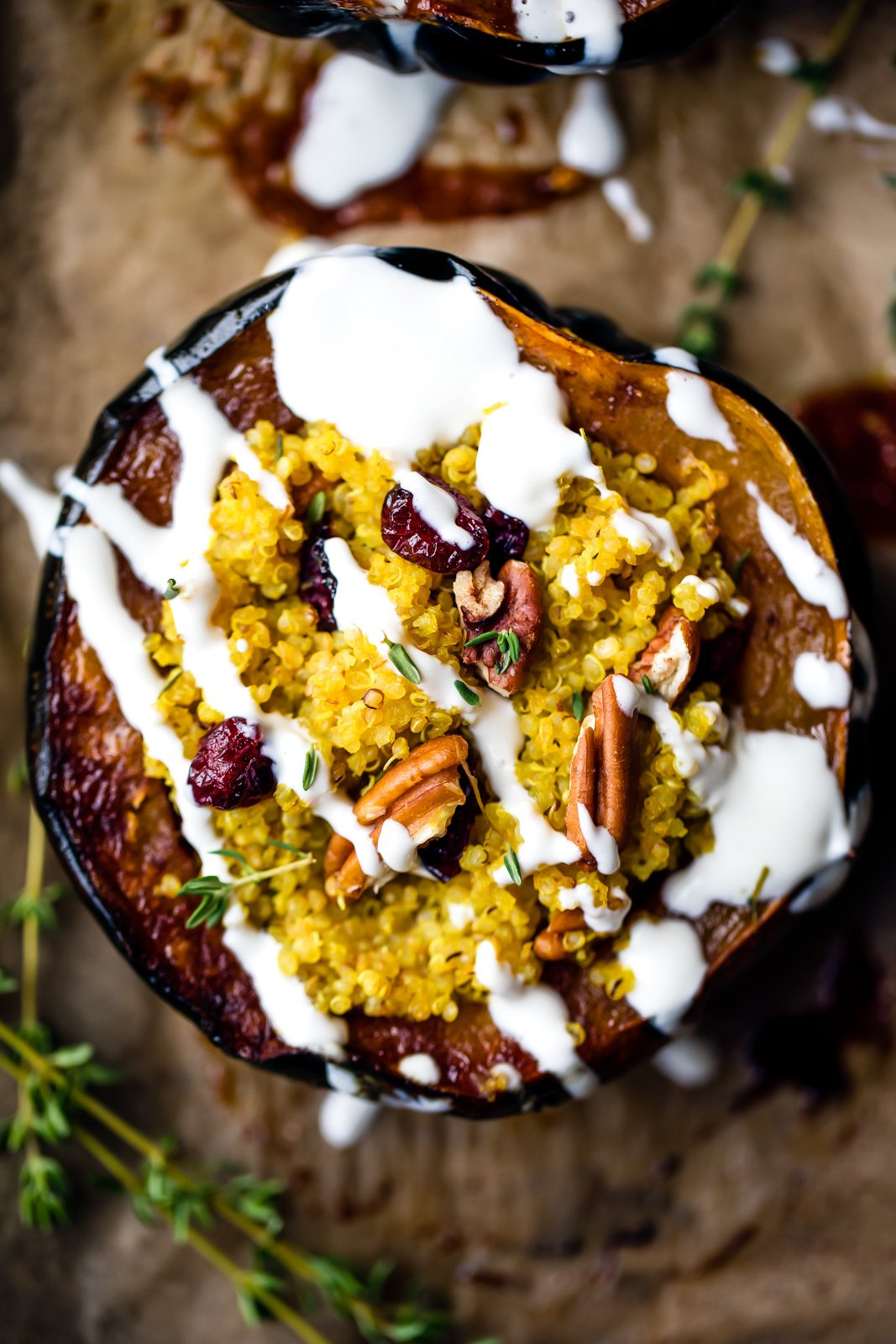 Stuffed acorn squash with cranberry, pecans and quinoa then drizzled with a simple goat cheese crema. Perfect for vegetarians at Thanksgiving, or anytime you're looking for a healthy plant based meal or side.