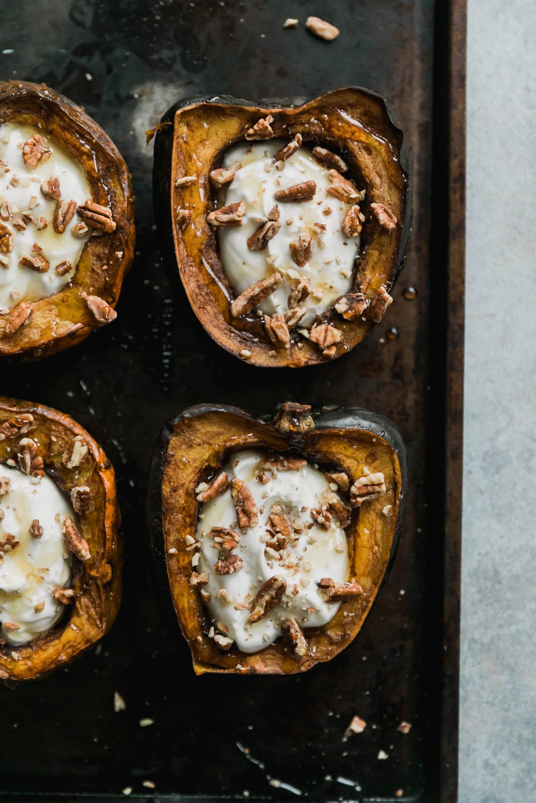 breakfast acorn squash stuffed with yogurt and pecans on a baking tray