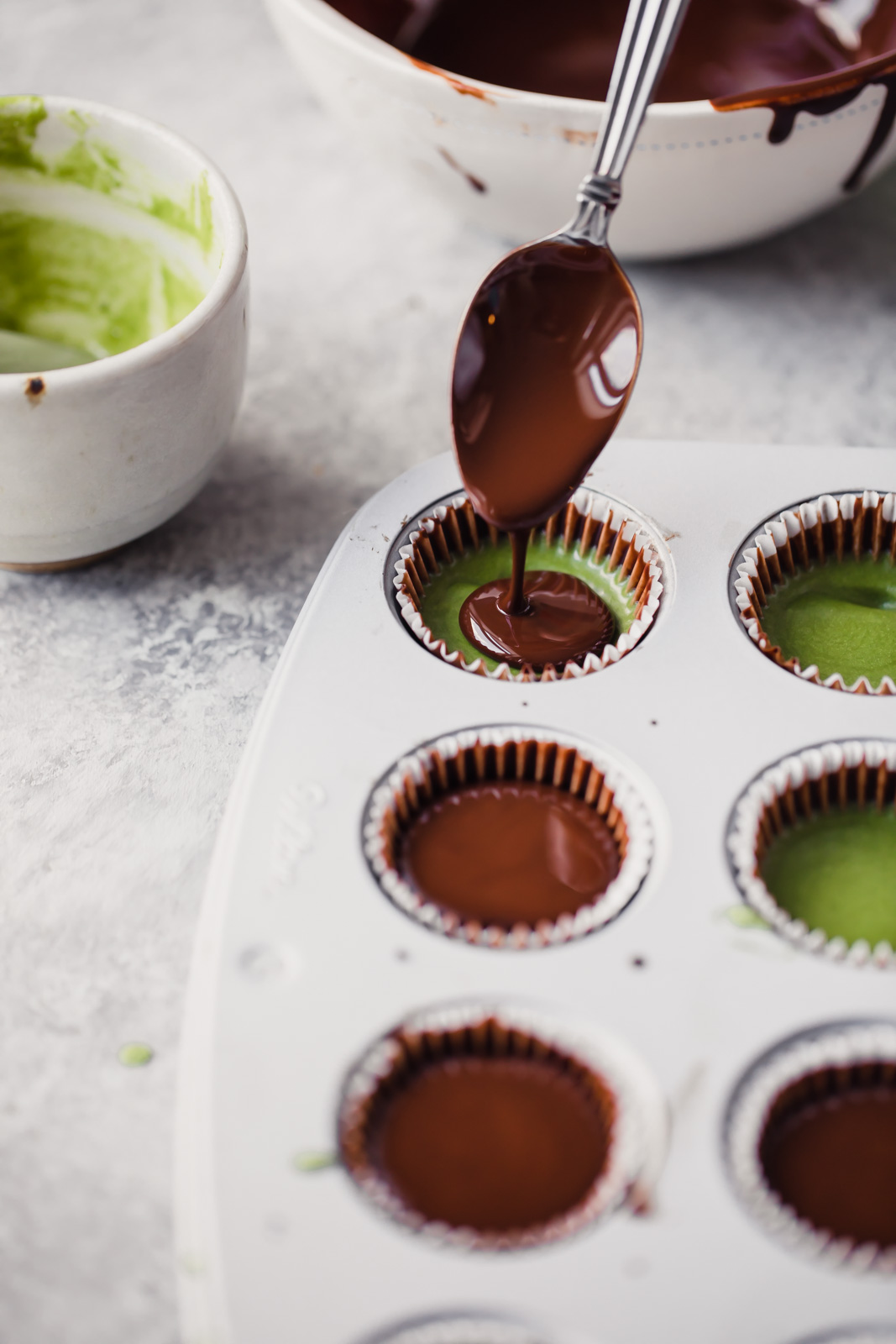 matcha dark chocolate coconut butter cups being made in a mini muffin tin