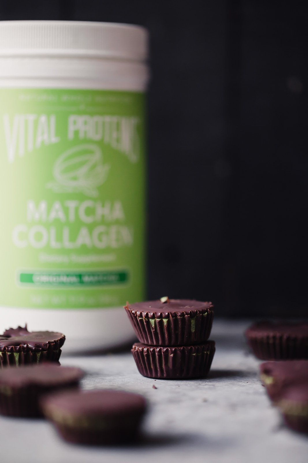 matcha dark chocolate coconut butter cups in a stack next to a green container of collagen