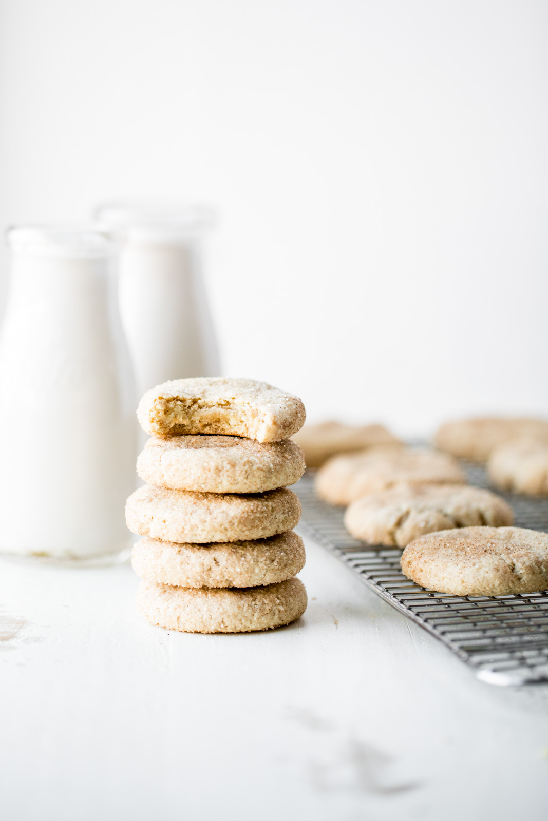 grain free snickerdoodles in a stack next to snickerdoodles on a wire rack