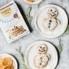 Grain free snowman pancakes on plates next to a box of pancake mix