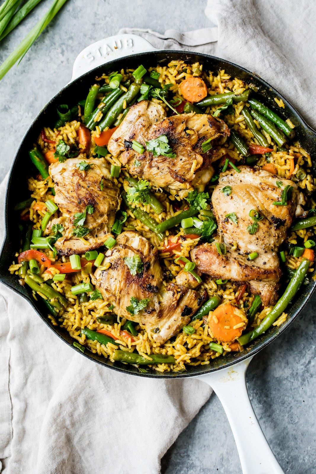 thai chicken yellow curry in a skillet pan with green beans