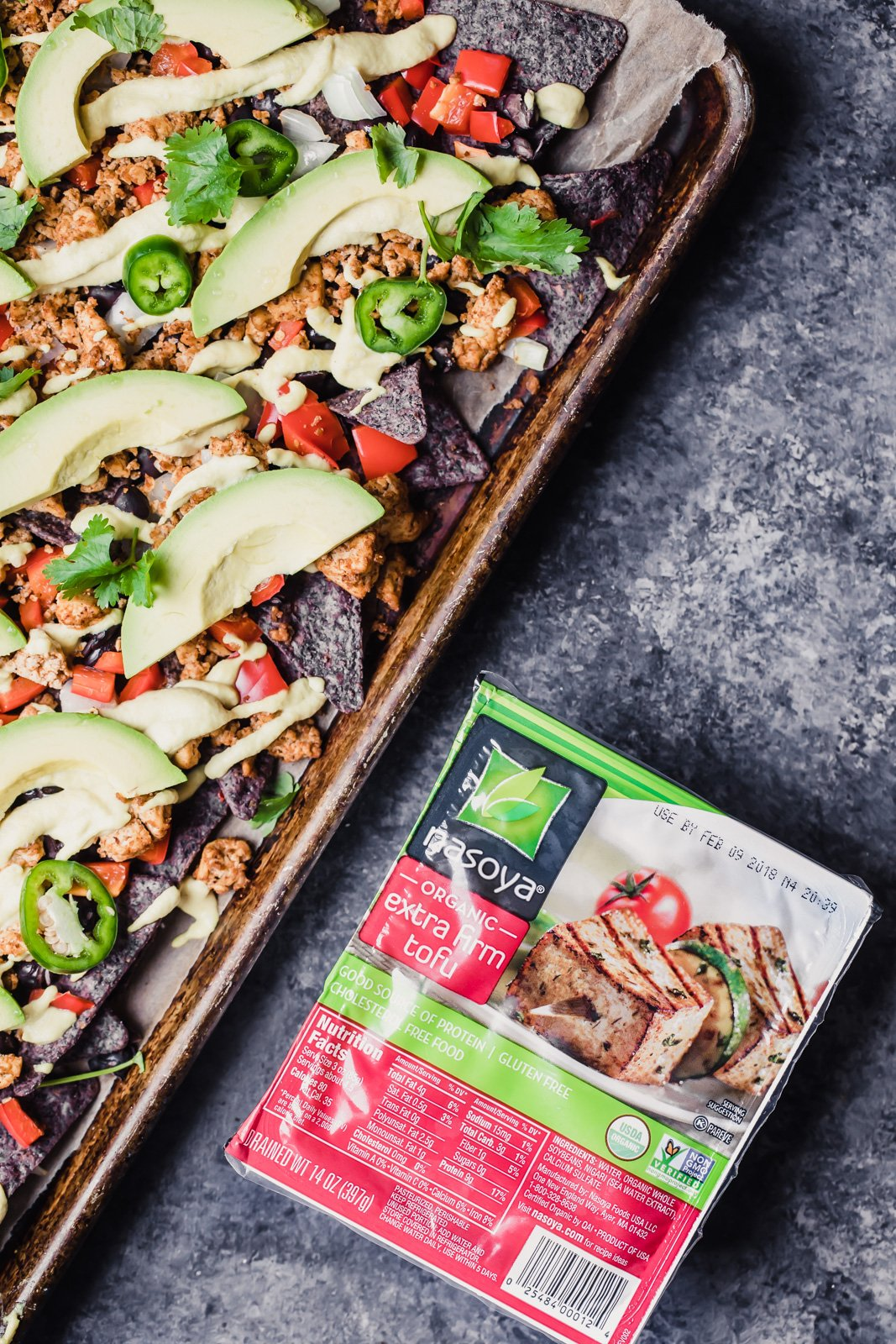 vegan nachos on a baking tray next to a package of tofu