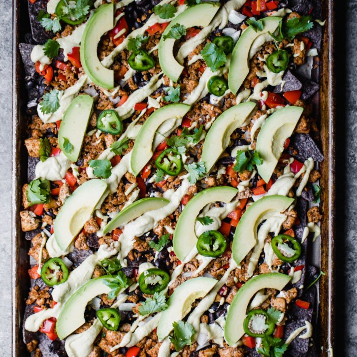 Beautiful vegan nachos with tofu taco meat and a creamy nacho cashew cheese sauce. Everyone will love these loaded nachos for their next favorite appetizer!
