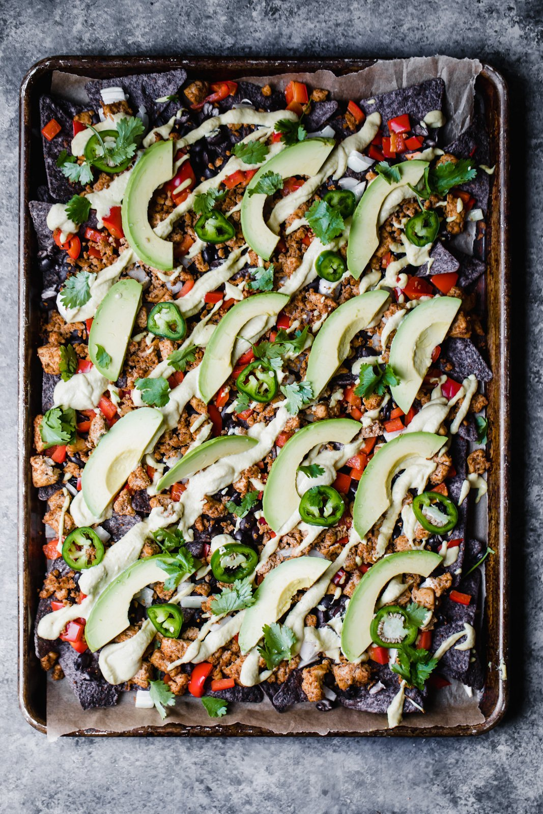 vegan nachos topped with avocado on a baking tray