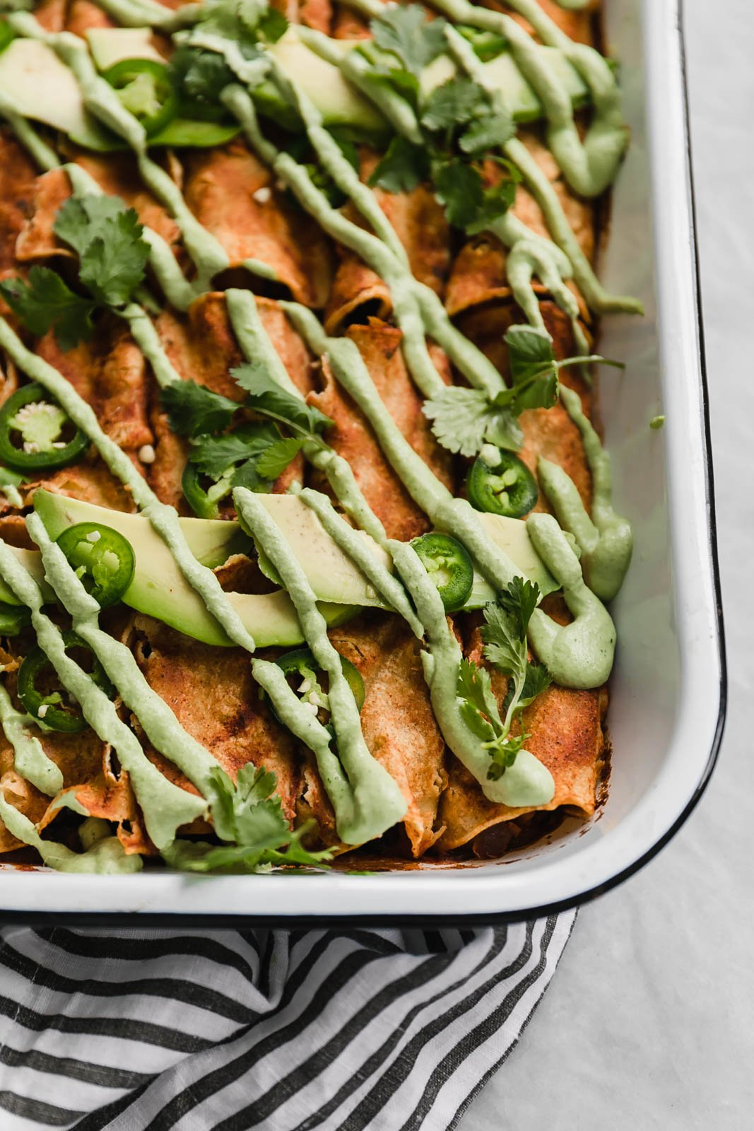 vegan enchiladas in a pan drizzled with jalapeño cashew crema