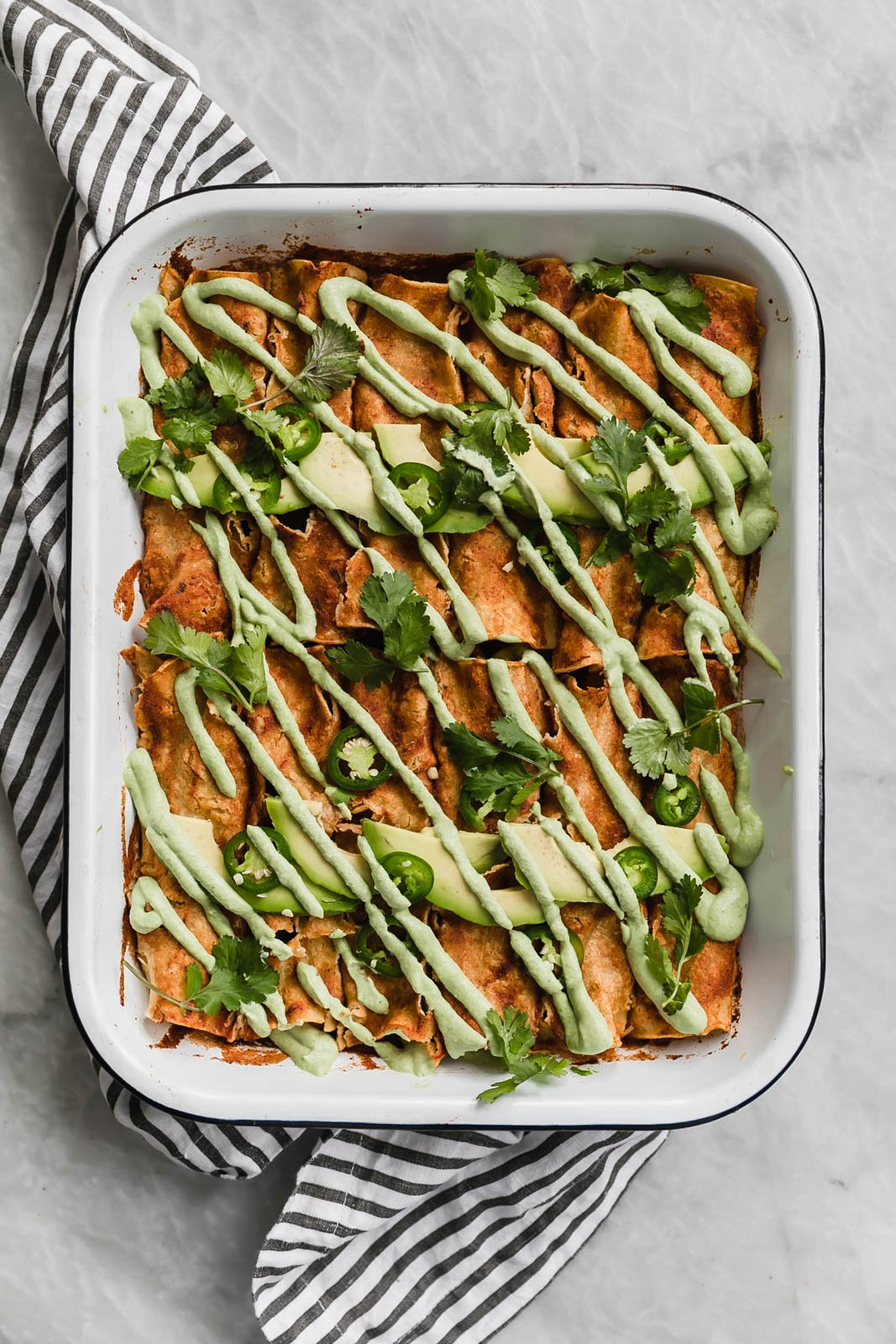 butternut squash enchiladas in a white baking dish topped with avocado, jalapeño and cilantro