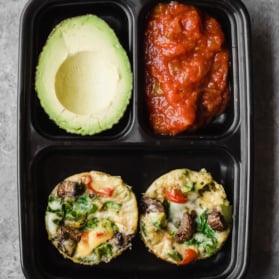 egg muffin cups in a container with avocado and salsa