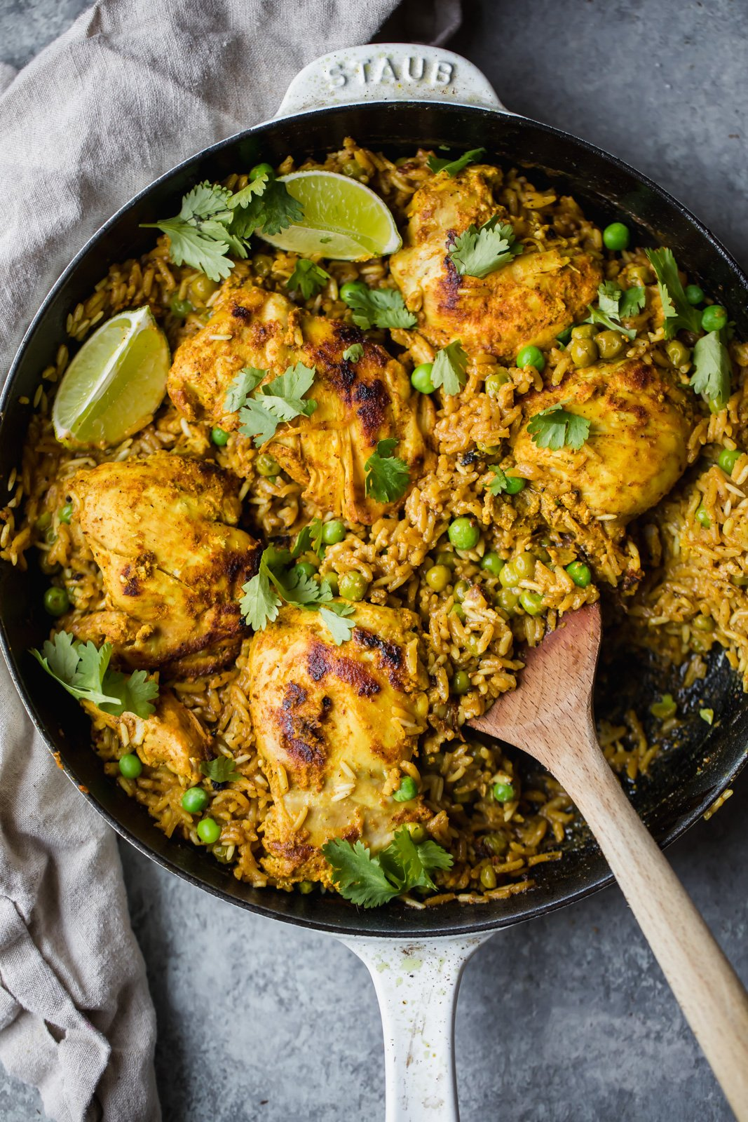 Tandoori chicken and rice in a pan with a wooden spoon
