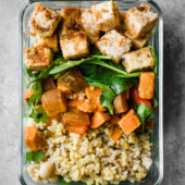 vegan tofu bowls in a meal prep container with rice and sweet potato