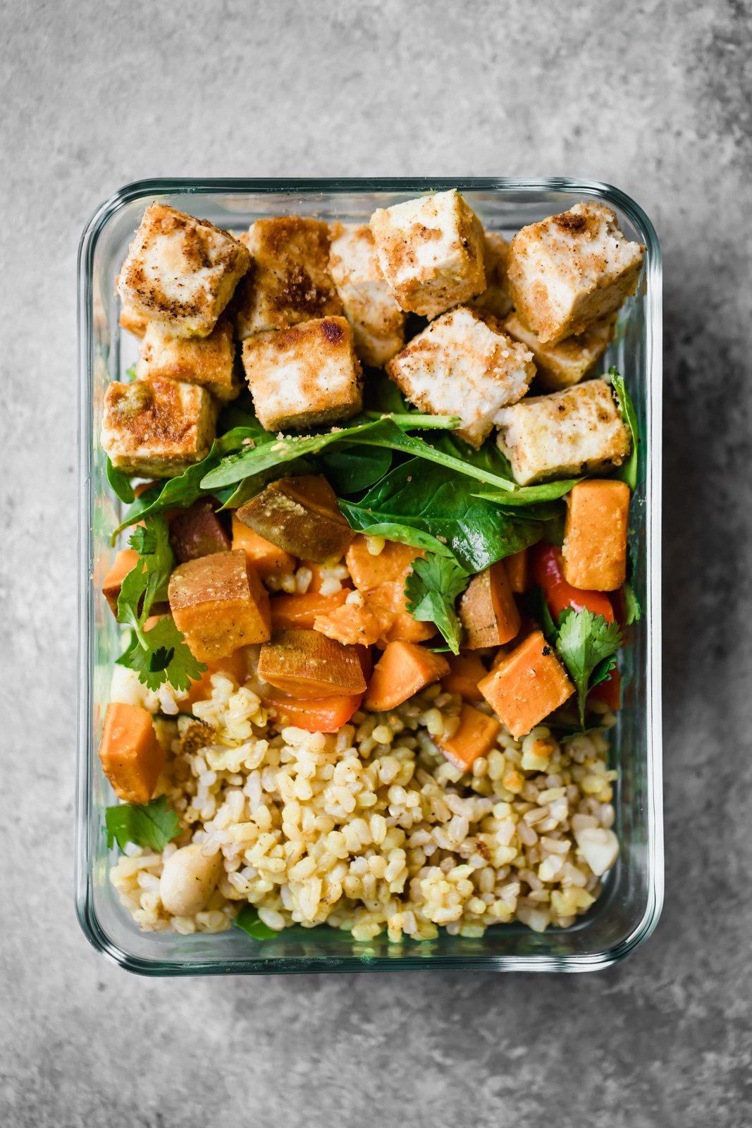 Vegan tofu bowls with sweet potato coconut milk sauce, spinach, sweet buttery macadamia nuts and brown rice. Made with organic Nasoya extra firm tofu. The perfect veggie packed lunch for meal prep!