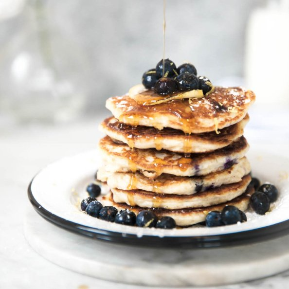 quinoa pancakes on a plate topped with blueberries