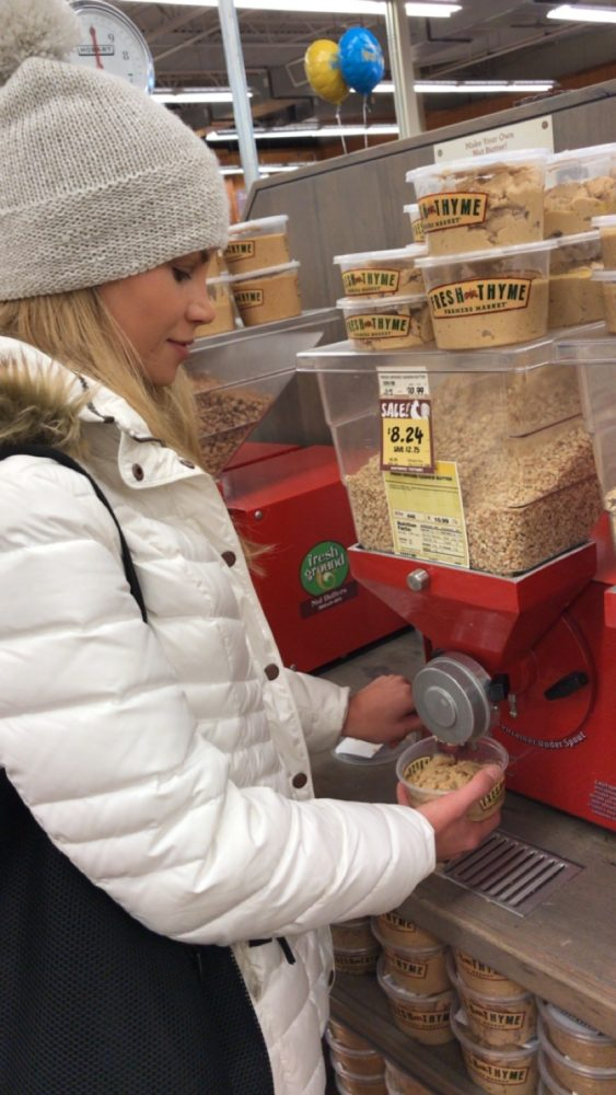Woman using machine that grinds peanuts into peanut butter