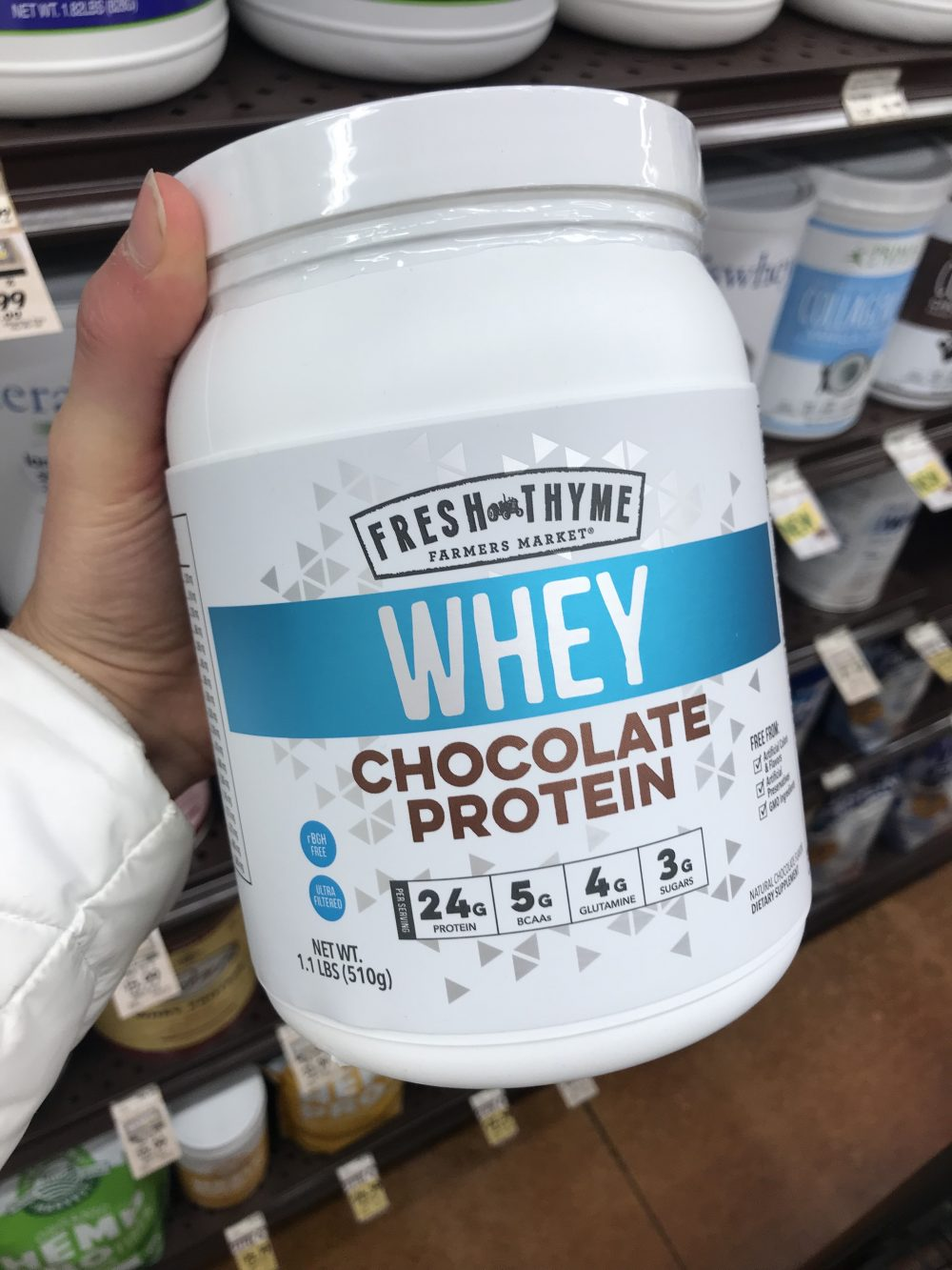 Large white jar of chocolate protein powder