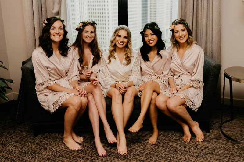 four bridesmaids and a bride sitting on a couch