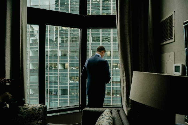 man in a tux next to the window of a hotel room