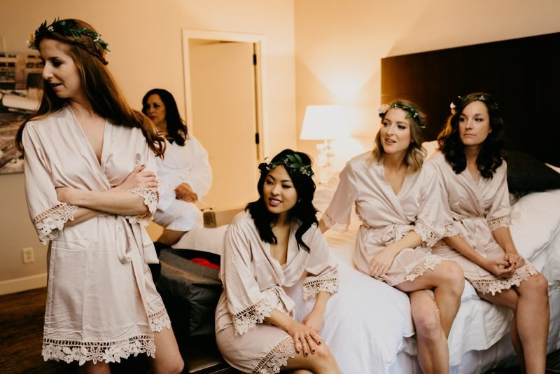 bridesmaids sitting on a hotel bed in pink robes