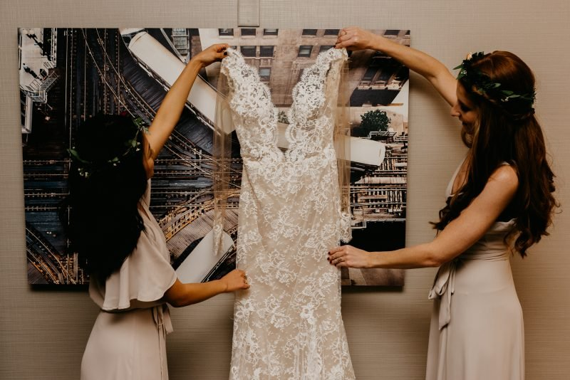 two bridesmaids holding up a wedding gown