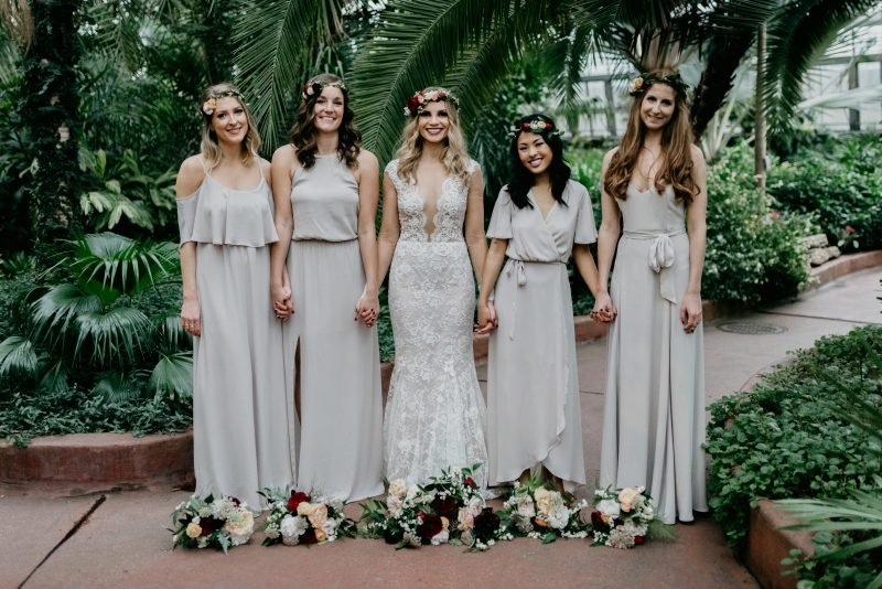 bride holding hands with four bridesmaids