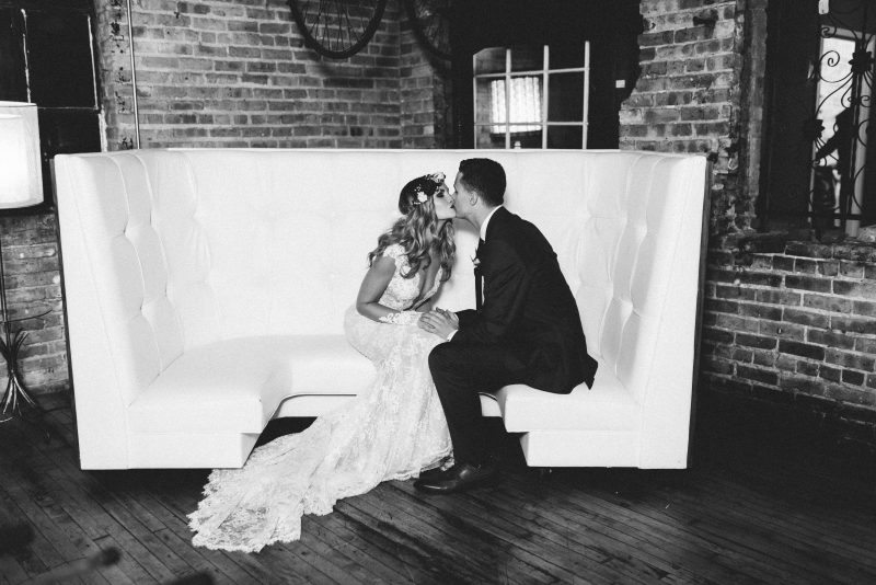 bride and groom kissing on a white couch
