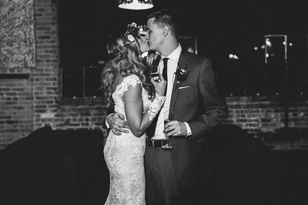 bride and groom kissing with champagne classes