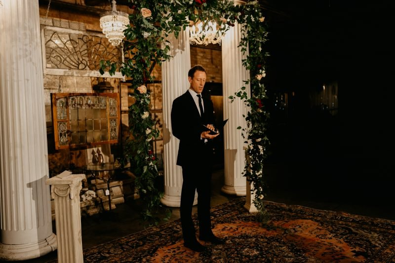 man speaking at the front of a wedding aisle